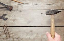 Att bulta spikar i träyttersida Plattången pennan, skiftnyckel och spikar beside arkivbilder