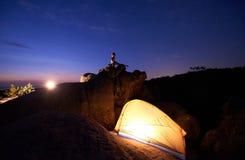 Att campa på natten vaggar på bildande Turist- tält och kvinna som gör yoga på bergöverkant arkivfoto