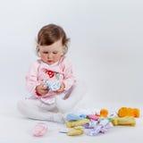 Att charma behandla som ett barn i ros som klänningen som spelar med, behandla som ett barn kläder Fotografering för Bildbyråer