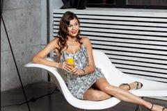 Att charma brunettflickan i en underbar grå aftonklänning sitter i en stilfull vit stol med ett exponeringsglas av fruktsaft royaltyfri bild