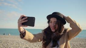 Att charma flickan är att filma videoen av henne vid den mobila kameran i solig strand arkivfilmer