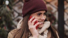 Att charma kvinnan ser lyckligt samtal på telefonen, medan hon står på gatan nära shoppar fönstret vinter för blommasnowtid arkivfilmer