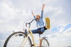 Att cykla ger dig mening av frihet och självständighet Bakgrund för himmel för flickarittcykel Frihet och fröjd Kvinna arkivfoton