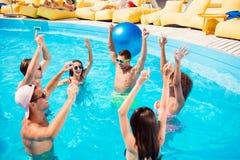 Att dansa internationell ungdom spelar med de enorma gummiblåtten Arkivbild