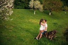 Att datera in parkerar Älska par som tillsammans står på gräs nära sjön attraktiva par som kramar kyssande förälskelse, gömma i h Arkivbilder