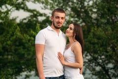 Att datera in parkerar Älska par som tillsammans står på gräs nära sjön attraktiva par som kramar kyssande förälskelse, gömma i h Royaltyfri Bild