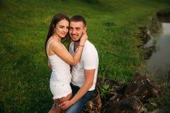 Att datera in parkerar Älska par som tillsammans står på gräs nära sjön attraktiva par som kramar kyssande förälskelse, gömma i h Arkivbild