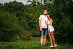 Att datera in parkerar Älska par som tillsammans står på gräs nära sjön attraktiva par som kramar kyssande förälskelse, gömma i h Royaltyfria Bilder