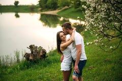 Att datera in parkerar Älska par som tillsammans står på gräs nära sjön attraktiva par som kramar kyssande förälskelse, gömma i h Royaltyfri Fotografi