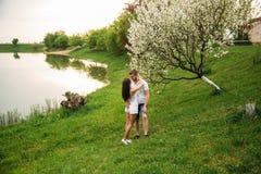 Att datera in parkerar Älska par som tillsammans står på gräs nära sjön attraktiva par som kramar kyssande förälskelse, gömma i h Royaltyfri Foto