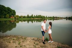 Att datera in parkerar Älska par som tillsammans står på jordning nära sjön attraktiva par som kramar kyssande förälskelse, gömma Arkivbilder