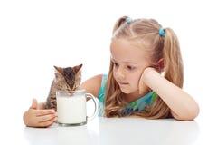 Att dela för liten flicka mjölkar med henne kattungen Arkivbild