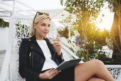 Att drömma den moderna affärskvinnan sitter med handlagblocket i kafé arkivfoto