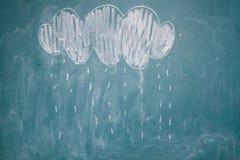 Att dra av regnar att falla från molnet på den svart tavlan royaltyfri bild