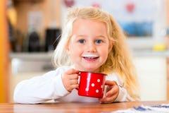 Att dricka för flicka mjölkar i kök Arkivbilder