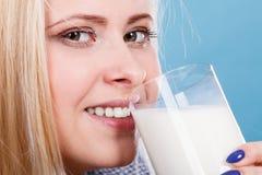 Att dricka för kvinna mjölkar från exponeringsglas Arkivbild