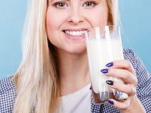 Att dricka för kvinna mjölkar från exponeringsglas Fotografering för Bildbyråer