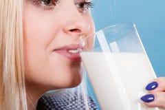 Att dricka för kvinna mjölkar från exponeringsglas Royaltyfria Bilder