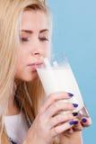 Att dricka för kvinna mjölkar från exponeringsglas Royaltyfri Foto