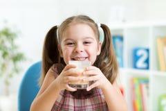 Att dricka för liten flicka mjölkar från glass inomhus Royaltyfri Foto