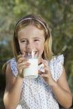 Att dricka för liten flicka mjölkar utomhus royaltyfri fotografi