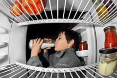 Att dricka för pojke mjölkar på kylskåpet royaltyfri foto