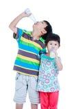 Att dricka för pojke och för flicka för två asiat mjölkar, isolerat på vit Drinkin Arkivfoto