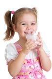 Att dricka för ungeflicka mjölkar eller yoghurten från exponeringsglas Fotografering för Bildbyråer