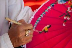 Att färga målar paraplyet som göras av papper/tyg. Konster och Royaltyfria Bilder