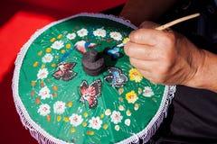 Att färga målar paraplyet som göras av papper/tyg. Konster och Fotografering för Bildbyråer
