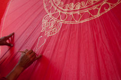 Att färga målar paraplyet som göras av papper/tyg. Konster och Arkivbild