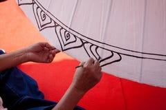 Att färga målar paraplyet som göras av papper/tyg. Konster och Arkivfoto