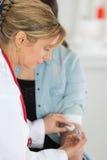 Att förbinda för sjuksköterska mans armen efter bloddonation Royaltyfri Bild