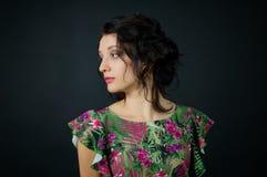 Att förbluffa den sexiga unga kvinnan med makeup och en trendig frisyr poserar i studio på svart bakgrund som bär den gröna klänn fotografering för bildbyråer