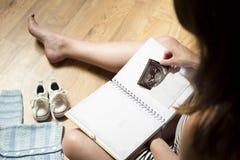 Att förlägga för kvinna behandla som ett barn sonogram för ` s in i behandla som ett barn för årsminnet för ` s den första boken Royaltyfria Foton
