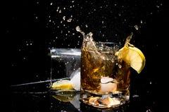 Att falla av is i exponeringsglas av whisky och gör många färgstänk och ett annat exponeringsglas som ligger på sida med citronsk Royaltyfri Fotografi