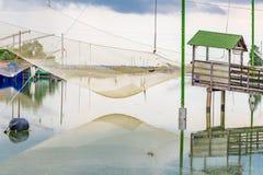 Att fiska förlägga i barack i tystnaden av den bräckta lagun Arkivbilder