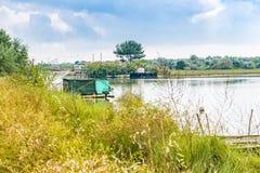 Att fiska förlägga i barack i tystnaden av den bräckta lagun Arkivbild