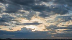 Att flytta sig fördunklar över fält en solnedgång, med sol- strålar lager videofilmer