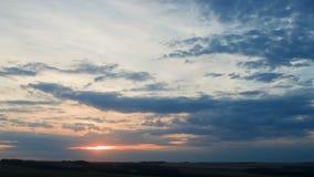Att flytta sig fördunklar över fält en solnedgång, timelapse arkivfilmer