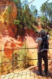 Att fotografera den färgrika ockran vaggar, Roussillon, Frankrike royaltyfria bilder
