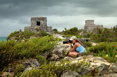 Att fotografera för kvinna som är karibiskt, seglar utmed kusten för regna mot Arkivfoton