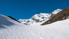 Att fotvandra för alpinist skidar turnera på snöig lutning in mot bergtoppmötet Begrepp av att erövra motgångar och att nå målet Arkivbild