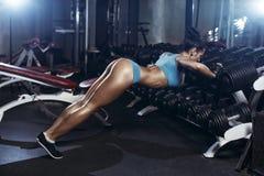 Att göra för konditionkvinna skjuter upp i idrottshallen Arkivfoto