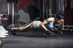 Att göra för konditionkvinna skjuter upp i idrottshallen Arkivbild