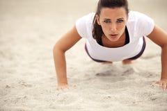 Att göra för kvinna skjuter upp övning på stranden Royaltyfria Bilder
