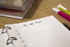 Att att göra listan som är skriftlig på ett papper arkivfoto