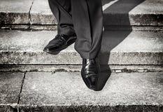 Affärsmannen lägger benen på ryggen att ta kliver på ett lägre jämnar på trappa Arkivbilder