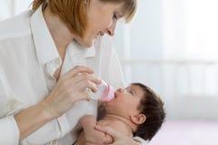 Att ge sig för mamma behandla som ett barn vatten från flasksammanträdet på sängen Arkivbild