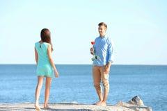 Att ge sig för ung man steg till hans flickvän nära havet Arkivfoto